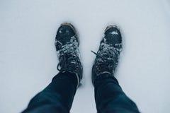 Jambes masculines dans des bottes d'hiver sur la surface neigeuse Photographie stock libre de droits