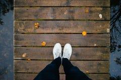 Jambes masculines dans des espadrilles sur le pont en bois par automne Photo stock