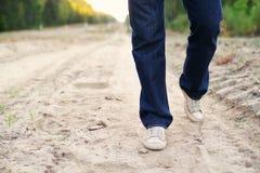 Jambes masculines dans les blues-jean et des chaussures de gymnase sur la route poussiéreuse arénacée Image libre de droits