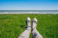 Jambes masculines dans les jeans et des espadrilles sur l'herbe fraîche contre le littoral Photos libres de droits