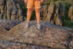 Jambes masculines de photo dans des chaussures en caoutchouc sur le fond du canyon Images stock