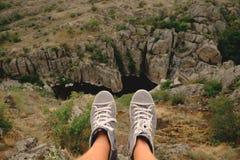 Jambes masculines de photo dans des chaussures en caoutchouc sur le fond du canyon Photo libre de droits