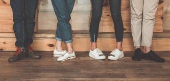Jambes masculines et femelles se tenant sur le plancher en bois Photos libres de droits