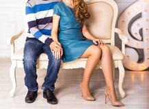 Jambes masculines et femelles sur le plan rapproché de sofa Image libre de droits