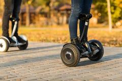 Jambes masculines sur de scooter le gyroscooter électrique dehors Photos stock