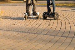 Jambes masculines sur de scooter le gyroscooter électrique dehors Photographie stock