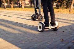 Jambes masculines sur de scooter le gyroscooter électrique dehors Image libre de droits