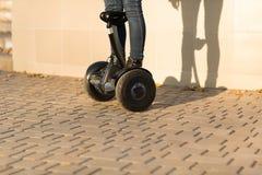 Jambes masculines sur de scooter le scooter électrique de compas gyroscopique dehors Images stock