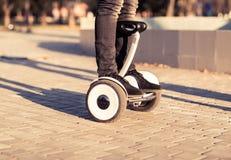 Jambes masculines sur de scooter le scooter électrique de compas gyroscopique dehors Photos libres de droits