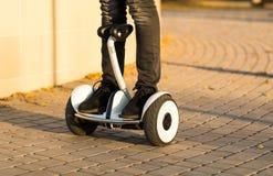 Jambes masculines sur de scooter le scooter électrique de compas gyroscopique dehors Images libres de droits