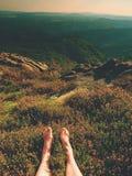 Jambes masculines sur le buisson sec de bruyère Jambes fatiguées sur le paysage maximal rocheux de bove Peau rose pure, clous cla Photos stock