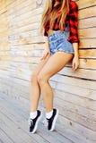 Jambes minces bronzages sexy chaudes de femme dans des shorts d'espadrilles et de jeans - clos Photo libre de droits