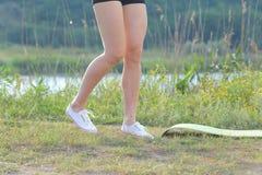 Jambes minces de photo de fille en bref et d'espadrilles en bois près Photographie stock libre de droits
