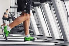 Jambes musculaires du ` s d'hommes sur un plan rapproché de tapis roulant photographie stock libre de droits