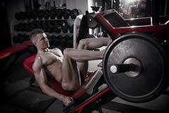 Jambes musculaires Séance d'entraînement belle de bodybuilder sur l'entraîneur dans le gymnase Photos libres de droits