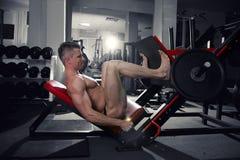 Jambes musculaires, séance d'entraînement belle de bodybuilder sur l'entraîneur dans le gymnase Photo libre de droits