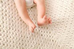 Jambes nouveau-nées de bébé, pieds, pied sur une couverture tricotée Photographie stock libre de droits