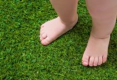 Jambes nues de bébé se tenant sur l'herbe verte Photographie stock