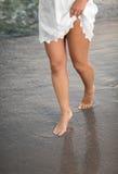 Jambes parfaites du ` s de femme sur la plage de sable et l'eau de mer Jambes sexy du ` s de femme sur la plage avec l'eau de mer Photographie stock