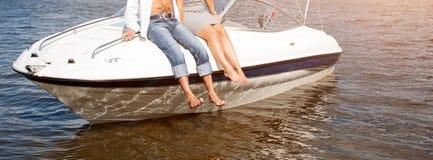 Jambes pendant du bateau flottant sur la rivière Aimez les couples ou les amis détendant sur un yacht, appréciant le soleil sur e Photographie stock libre de droits