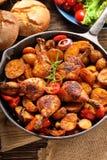 Jambes rôties de poulet avec la pomme de terre cuite au four sur la poêle photo libre de droits