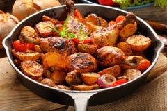 Jambes rôties de poulet avec la pomme de terre cuite au four sur la poêle photographie stock libre de droits