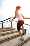 Jambes saines de femme de mode de vie fonctionnant sur les escaliers en pierre Images stock