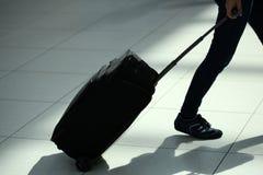 Jambes se déplaçant avec la valise de roulement Photographie stock libre de droits