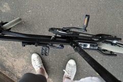 Jambes se tenant avec la bicyclette avec le moteur Photo stock