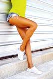 Jambes sexy de femme dans des shorts et des espadrilles de jeans Image libre de droits