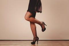 Jambes sexy de femme dans le noir Photos stock