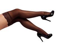 Jambes sexy de femme utilisant le collant et les talons hauts noirs Image libre de droits