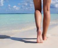 Jambes sexy sur la plage tropicale de sable. Pieds femelles de marche. Image stock