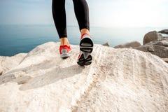 Jambes sportives de femme sur la plage rocheuse Photographie stock libre de droits
