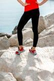 Jambes sportives de femme sur la plage rocheuse Photographie stock