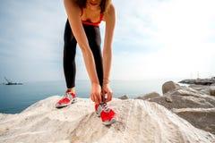 Jambes sportives de femme sur la plage rocheuse Photo stock