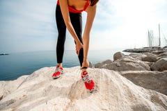 Jambes sportives de femme sur la plage rocheuse Image stock