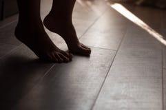 Jambes sur un plancher en bois chaud image stock