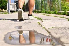 Jambes tout en marchant Réflexions dans l'eau sur le trottoir Photos stock