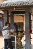 Jambi, Indonesia - 7 ottobre 2018: Un uomo sta pregando ai dei mettendo i bastoni di incenso al vaso del joss in un Vihara fotografia stock