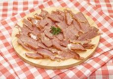 Jambon coupé en tranches appétissant sur la planche à découper Photos libres de droits