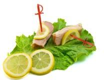 Jambon coupé en tranches sur des lames de salade avec le citron Photographie stock libre de droits