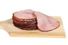 Jambon coupé en tranches sur la planche à découper Photo stock