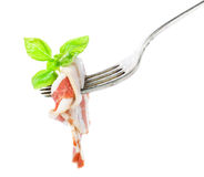 Jambon de Parme délicieux sur la fourchette argentée d'isolement sur le fond blanc Images stock