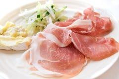 Jambon de Prosciutto avec du fromage et la salade à l'arrière-plan blanc Photographie stock libre de droits