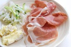 Jambon de Prosciutto avec du fromage et la salade à l'arrière-plan blanc Photos stock