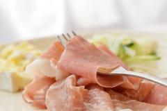 Jambon de Prosciutto avec du fromage et la salade à l'arrière-plan blanc Photo libre de droits
