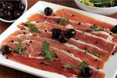 Jambon de Serrano avec les olives noires Photo libre de droits
