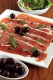 Jambon de Serrano et apéritif d'olives Photographie stock