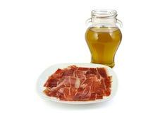 Jambon espagnol de serrano avec l'huile d'olive sur le blanc Photographie stock